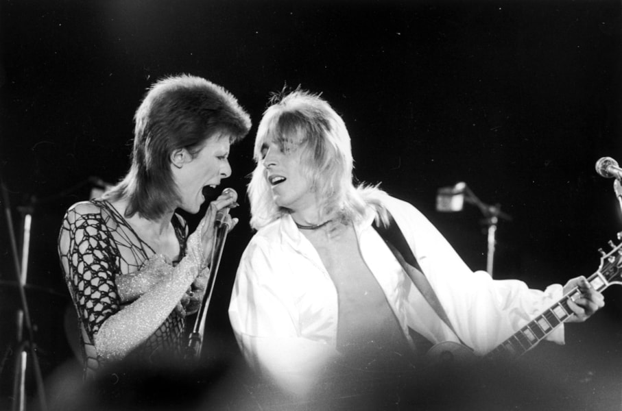 David Bowie (1947 - 2016, left) performing with guitarist Mick Ronson (1946 1993) at a live recording of 'The 1980 Floor Show' for the NBC 'Midnight Special' TV show, at The Marquee Club in London, with a specially invited audience of Bowie fanclub members, 20th October 1973. (Photo by Jack Kay/Daily Express/Getty Images)