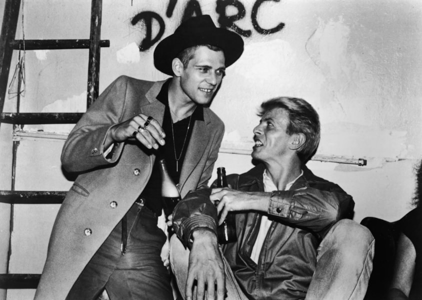 British rock singer and actor David Bowie (R) has a drink backstage with Paul Simonon, the bassist from British punk rock band The Clash, following the group's concert at Shea Stadium, Queens, New York City, circa 1982. (Photo by Hulton Archive/Getty Images)