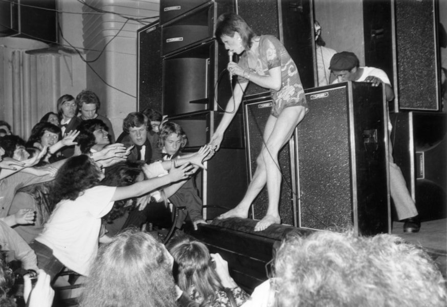 3rd July 1973:  Adoring fans reaching out to touch the hand of the English pop star, David Bowie, during the concert at the Hammersmith Odeon where Bowie announced that he was retiring his alter-ego 'Ziggy Stardust'.  (Photo by Steve Wood/Express/Getty Images)