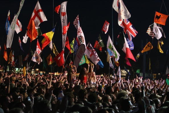 GLASTONBURY, ENGLAND - JUNE 27: Fans cheer as Bruce Springsteen performs on the main Pyramid Stage at the Glastonbury Festival at Worthy Farm, Pilton on June 27, 2009 near Glastonbury, England. (Photo by Matt Cardy/Getty Images)