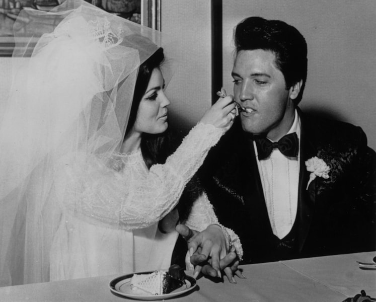 Elvis Presley (1935 - 1977) being fed a mouthful of wedding cake by his bride Priscilla Beaulieu at the Aladdin Hotel, Las Vegas.   (Photo by Keystone/Getty Images)