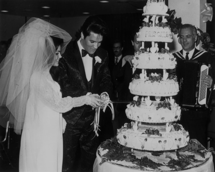 Elvis Presley (1935 - 1977) cutting the six-tier wedding cake with his bride Priscilla Beaulieu at the Aladdin Hotel, Las Vegas.   (Photo by Keystone/Getty Images)