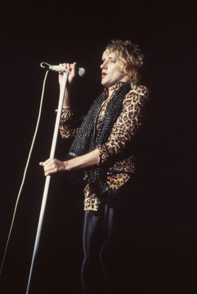 circa 1975:  Rock star Rod Stewart at the microphone wearing a 'leopard skin' shirt.  (Photo by Hulton Archive/Getty Images)
