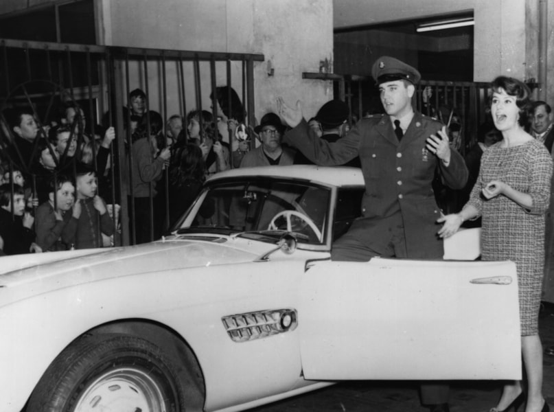 Fans watch as German TV celebrity Uschi Siebert presents American rock 'n' roll star Elvis Presley  (1935 - 1977) with the keys to the BMW sports car with which German racing driver Hans-Joachim Stuck won a number of world racing events. Presley is a PFC in the American Armed Forces, serving with a US armoured unit at Friedberg.  (Photo by Keystone/Getty Images)