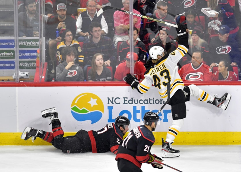 RALEIGH, NORTH CAROLINA - MAY 14: Justin Faulk #27 of the Carolina Hurricanes falls to the ice after colliding with Danton Heinen #43 of the Boston Bruins during the second period in Game Three of the Eastern Conference Finals during the 2019 NHL Stanley Cup Playoffs at PNC Arena on May 14, 2019 in Raleigh, North Carolina. (Photo by Grant Halverson/Getty Images)