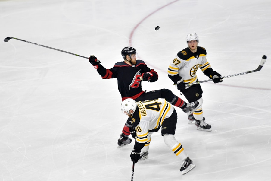 RALEIGH, NORTH CAROLINA - MAY 14: Warren Foegele #13 of the Carolina Hurricanes looks for the puck against Matt Grzelcyk #48 and Torey Krug #47 of the Boston Bruins during the third period in Game Three of the Eastern Conference Finals during the 2019 NHL Stanley Cup Playoffs at PNC Arena on May 14, 2019 in Raleigh, North Carolina. (Photo by Grant Halverson/Getty Images)