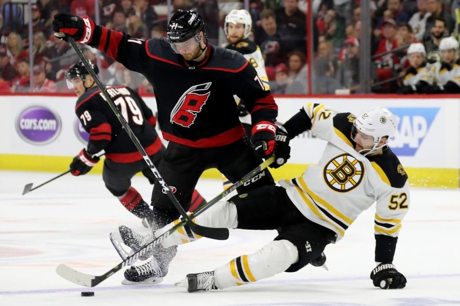 RALEIGH, NORTH CAROLINA - MAY 14: Lucas Wallmark #71 of the Carolina Hurricanes collides with Sean Kuraly #52 of the Boston Bruins during the third period in Game Three of the Eastern Conference Finals during the 2019 NHL Stanley Cup Playoffs at PNC Arena on May 14, 2019 in Raleigh, North Carolina. (Photo by Bruce Bennett/Getty Images)